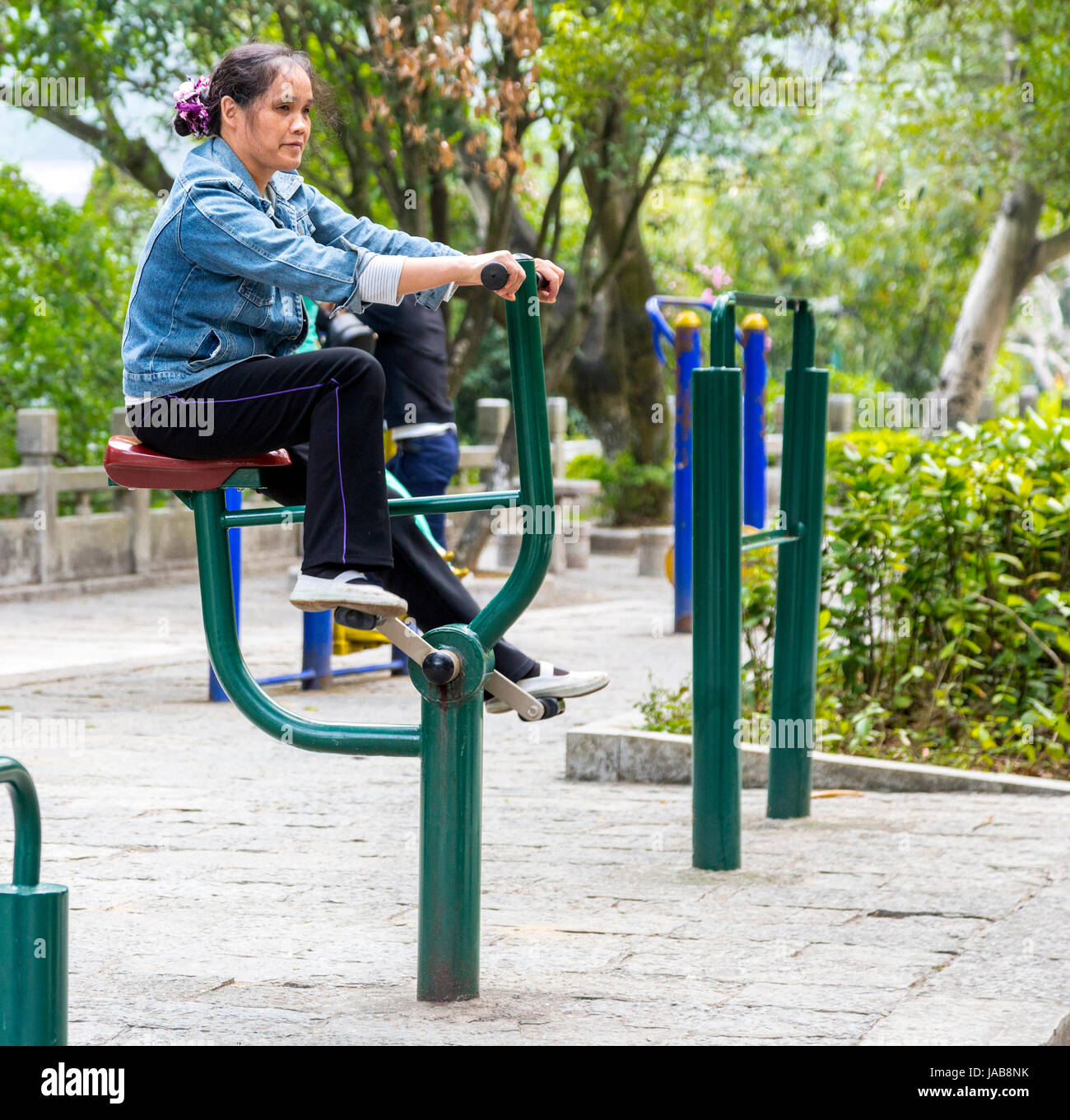 Yangshuo, Chine. Woman Working Out sur les appareils d'exercice. Photo Stock
