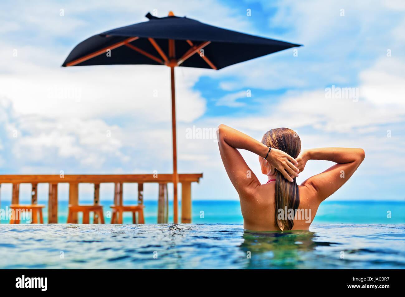 Jeune femme heureuse de s'amuser dans une piscine à débordement avec vue sur l'océan. Fille Photo Stock