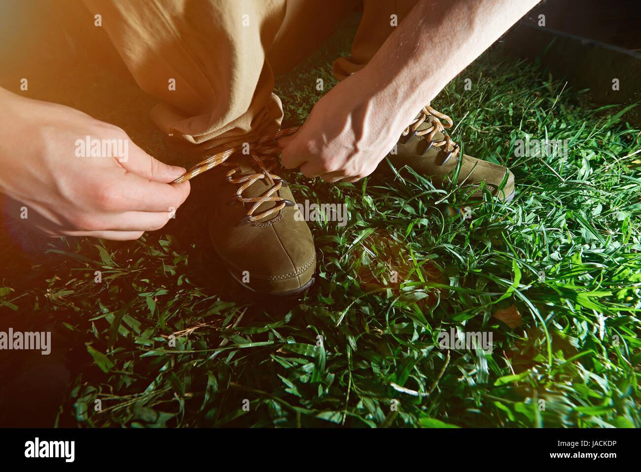 Lier l'homme sur ses lacets de chaussures active libre fond d'herbe verte Banque D'Images
