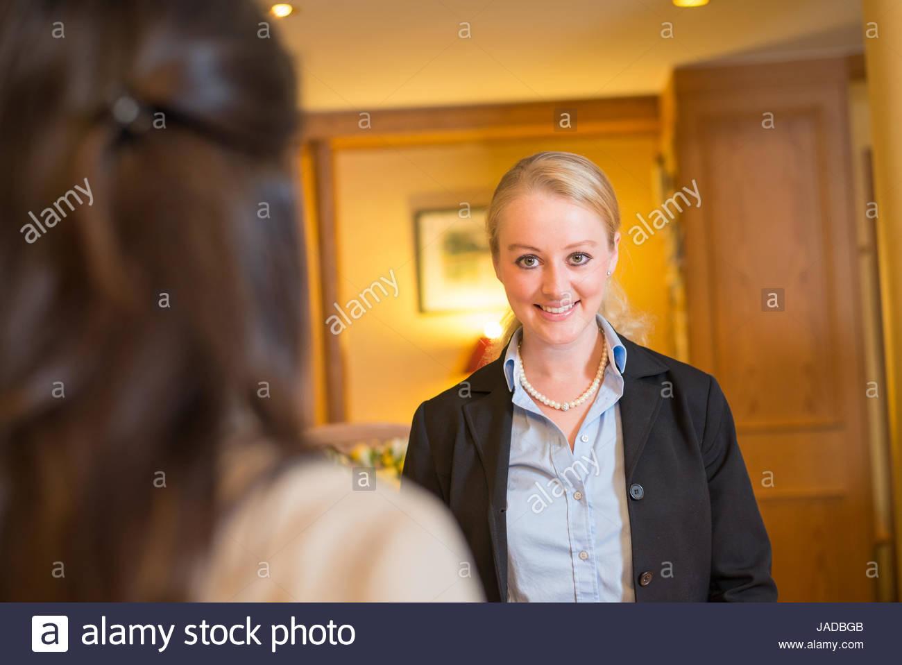 Belle blonde élégant hôtel réceptionniste debout derrière le bureau
