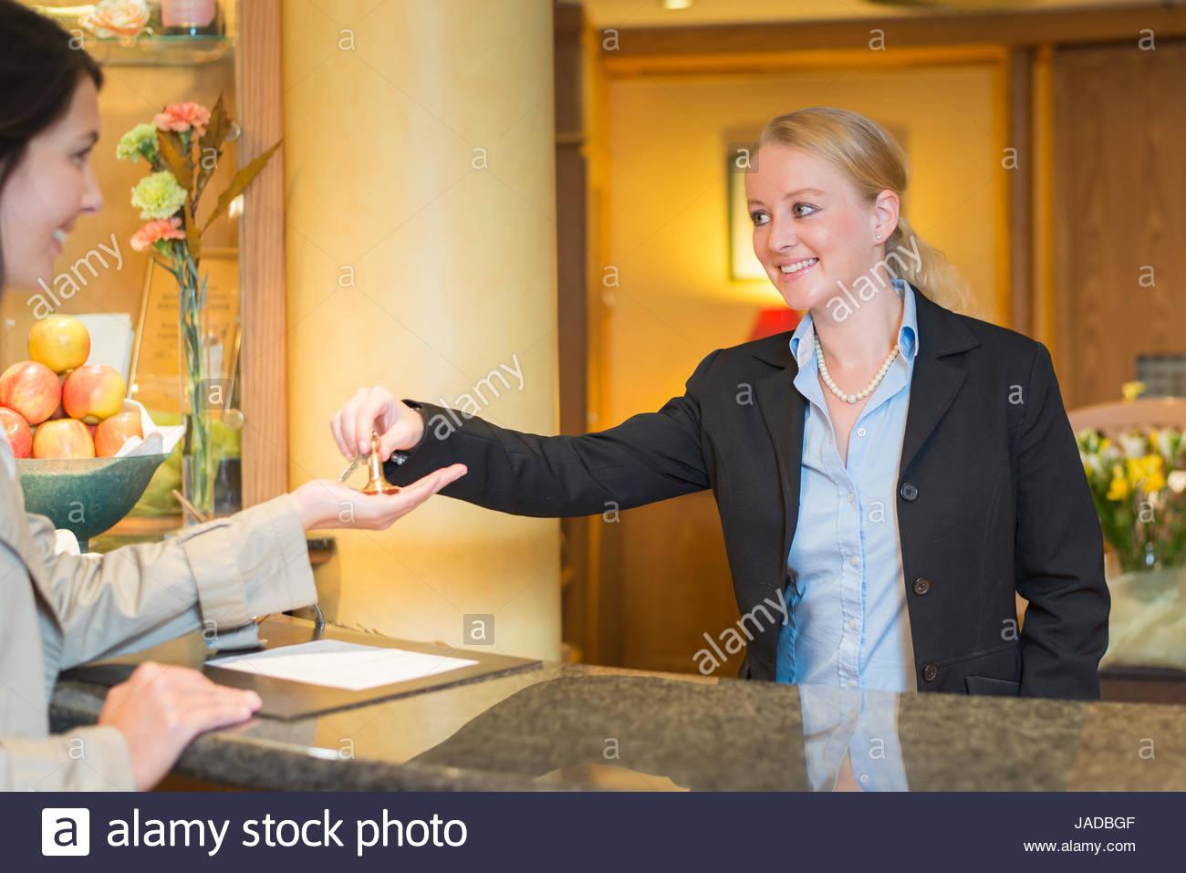 Cet hôtel réceptionniste souriant debout derrière le bureau