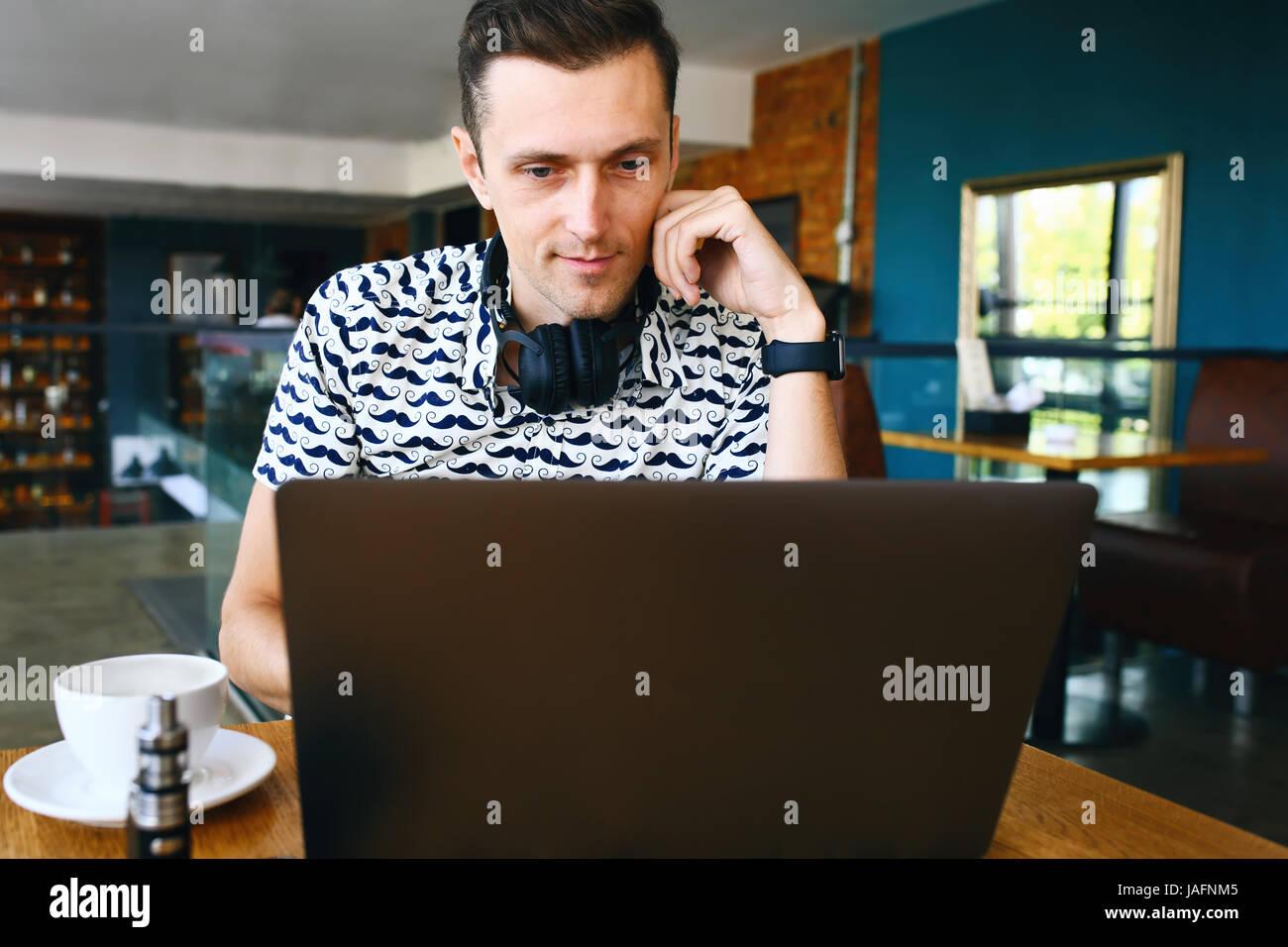 Attractive male travailleur est à l'aide d'ordinateur dans une cafétéria Photo Stock