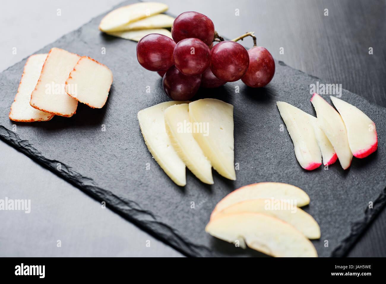 Plateau de fromages mixtes gastronomique starter tapas avec apple et le raisin snack Photo Stock