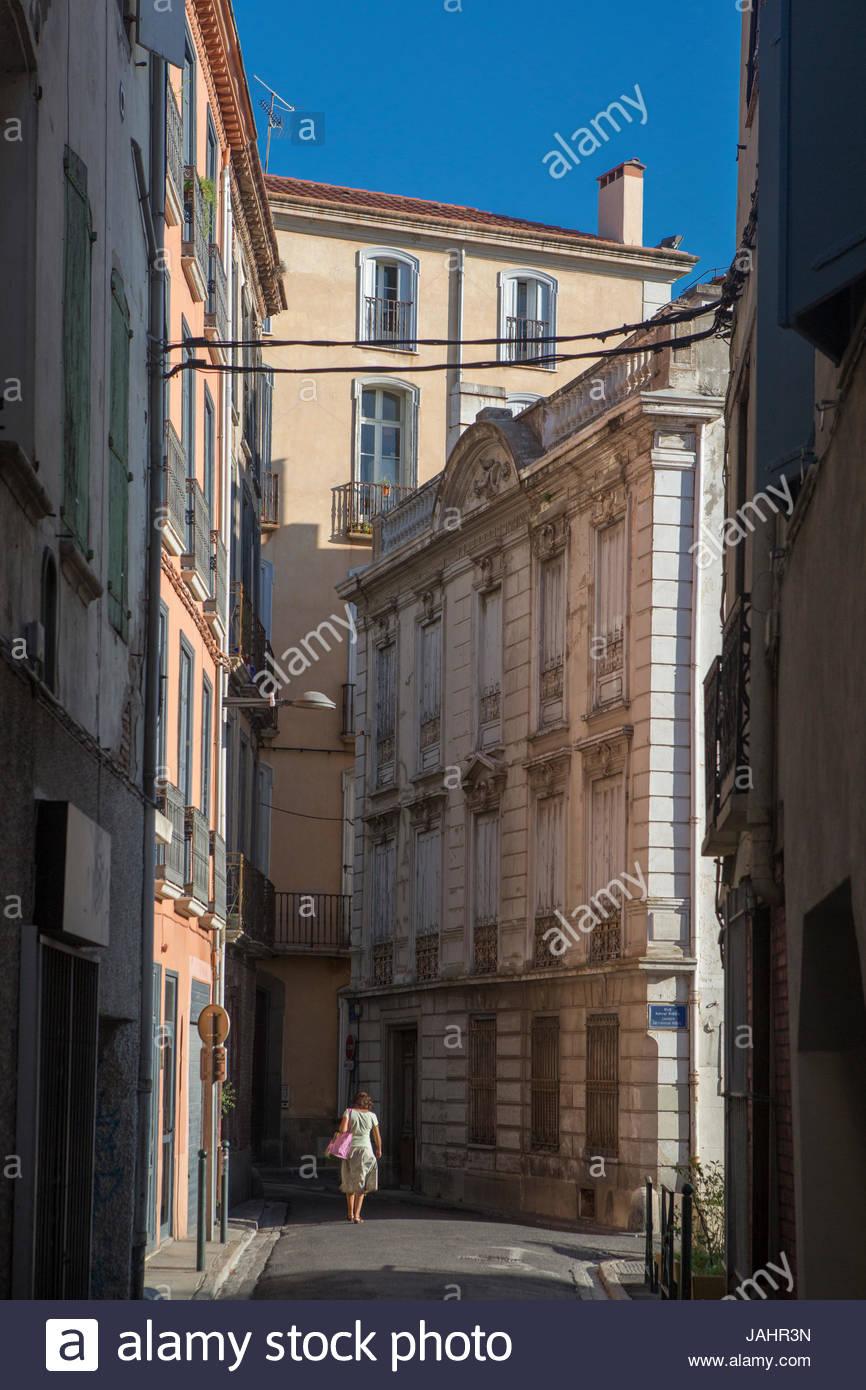 Une femme marchant sur une ruelle de la vieille ville de Perpignan, France. Photo Stock