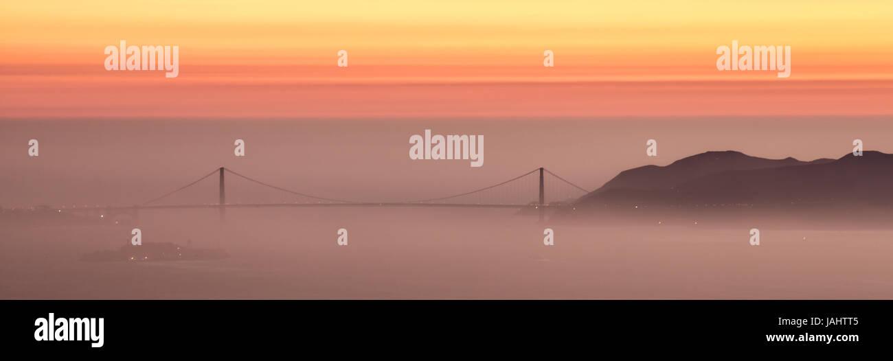 Ciel voilé, coucher de soleil sur le Golden Gate Bridge, San Francisco. Banque D'Images