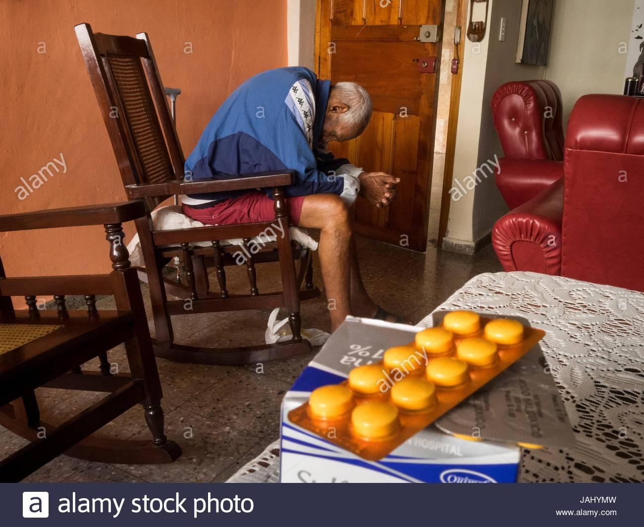 Des médicaments sur une table et un vieil homme endormi dans un fauteuil à bascule. Photo Stock