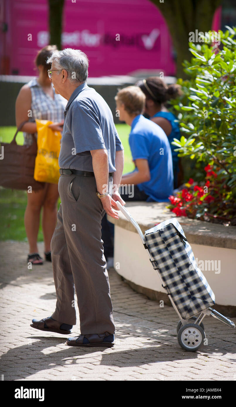 Ancien Senior citizen man walking in sunshine avec son panier avec de courtes manches longues sur avec les cheveux Photo Stock