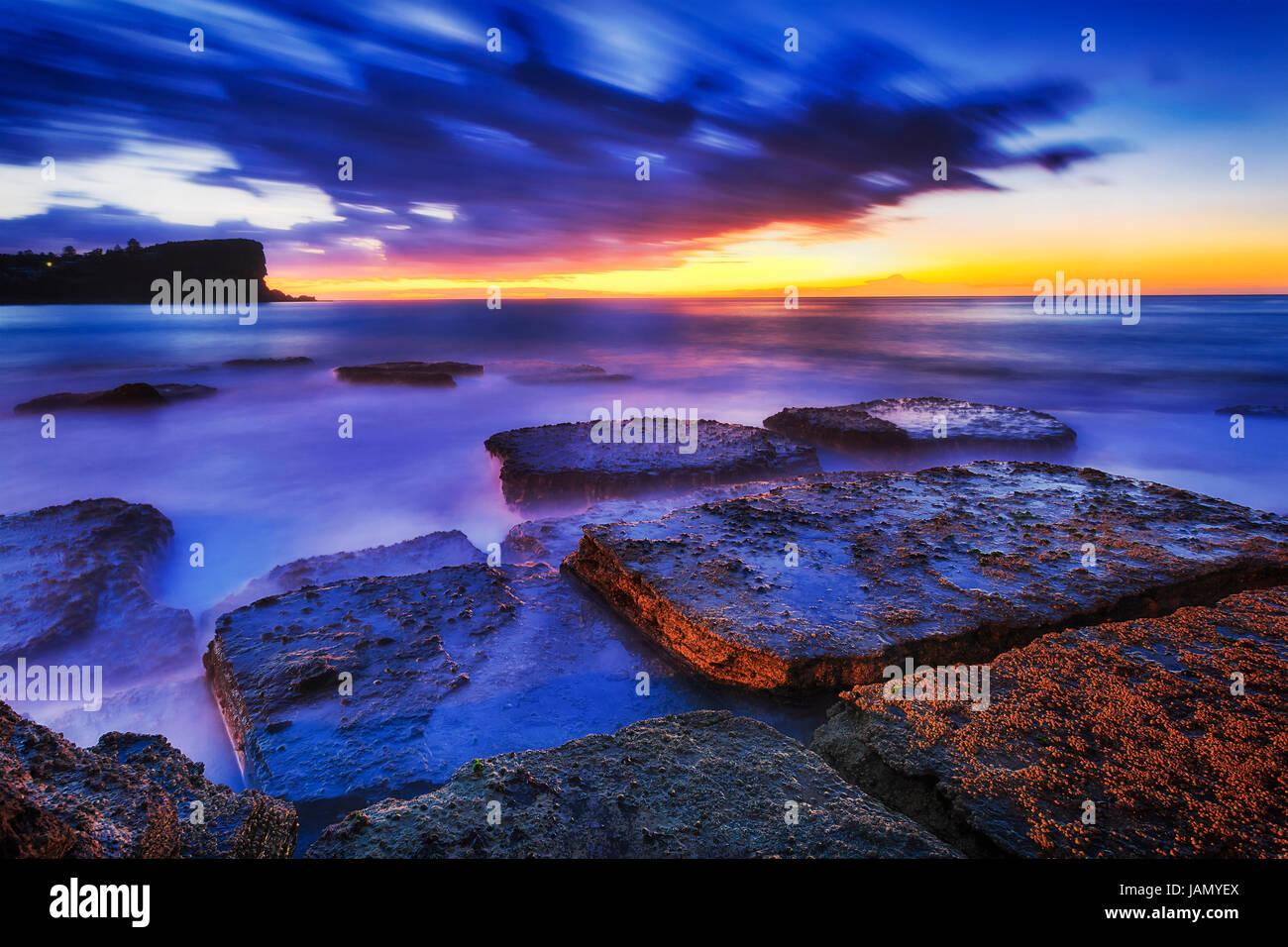 Lever de soleil sur l'heure bleu foncé à l'horizon de mer plage Avalon roches avec alga de plages Photo Stock
