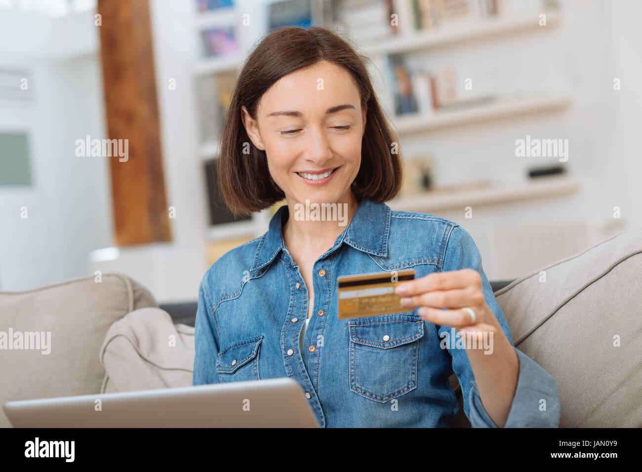 Femme avec un ordinateur portable connecté et le magasinage en ligne Photo Stock