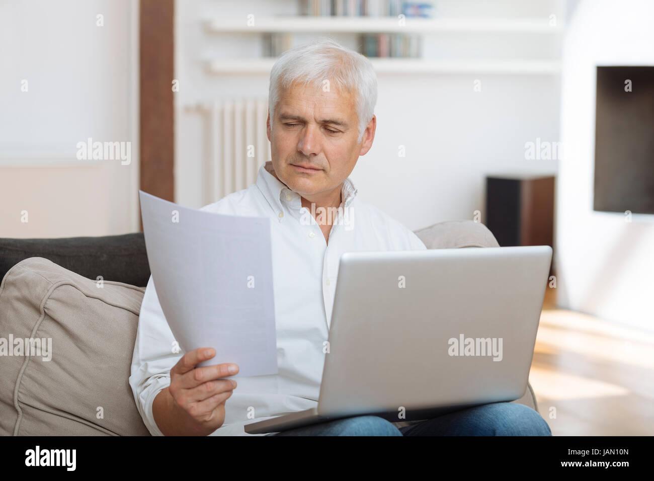 Homme mûr payer les factures en ligne Photo Stock