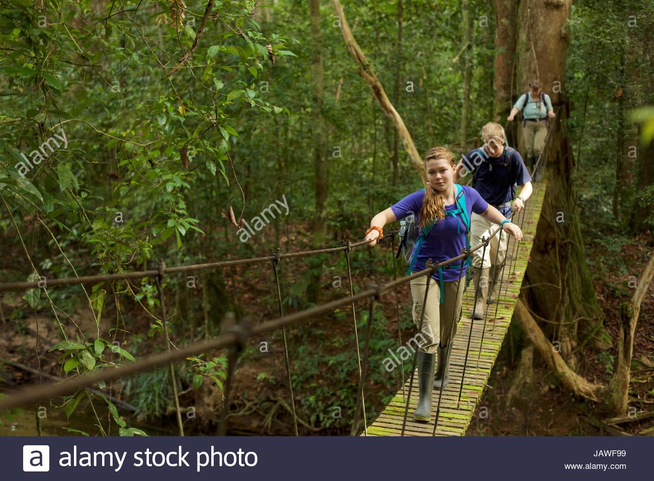 Un garçon et fille traverser un pont suspendu à Gunung Palung National Park. Photo Stock