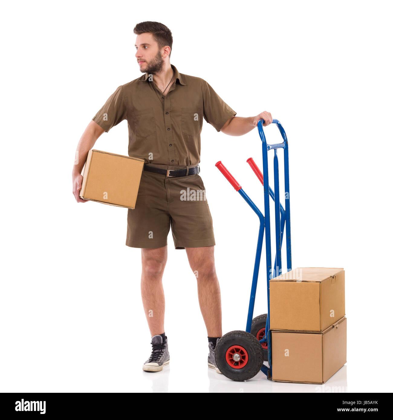 Courrier mâle est debout près de push cart, holding paquet sous le bras et à la voiture. Studio pleine longueur Banque D'Images