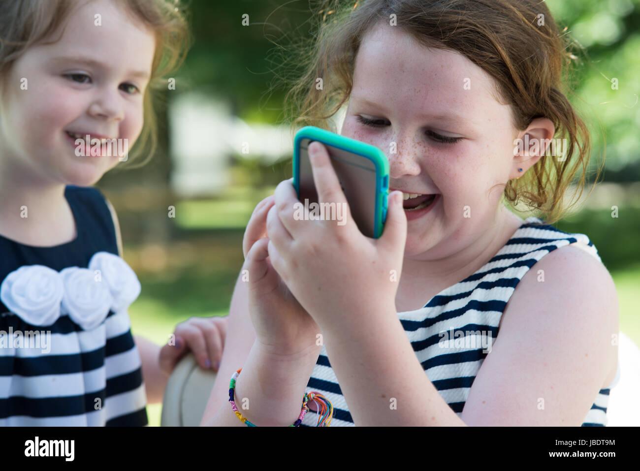Heureux rire des enfants qui jouent avec le smartphone à l'extérieur Photo Stock
