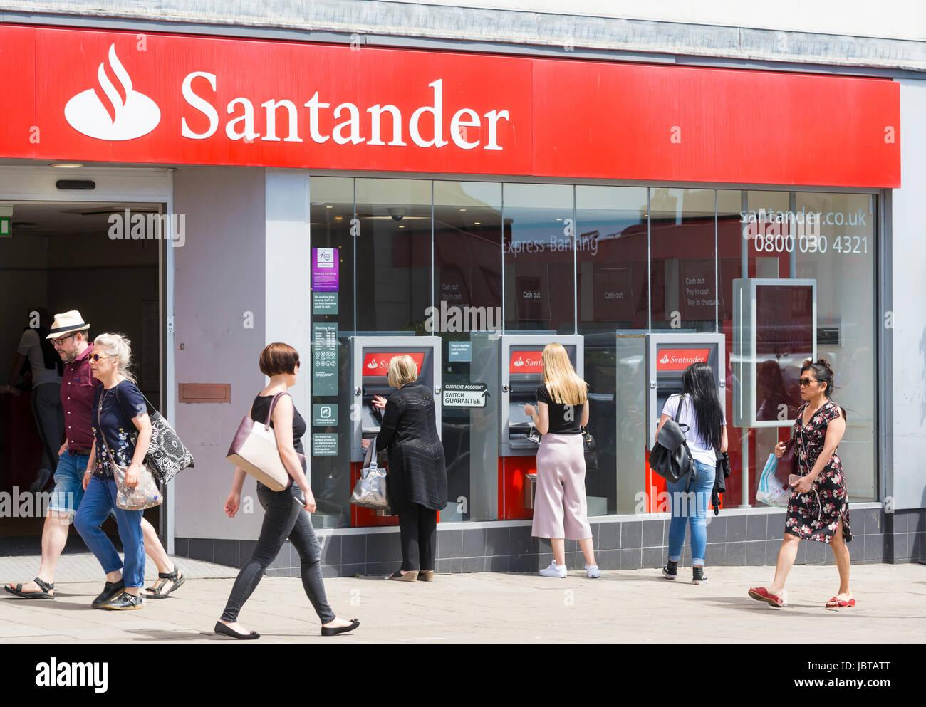 Dans une banque Santander UK high street avec les gens à l'aide de distributeurs automatiques. Banque D'Images