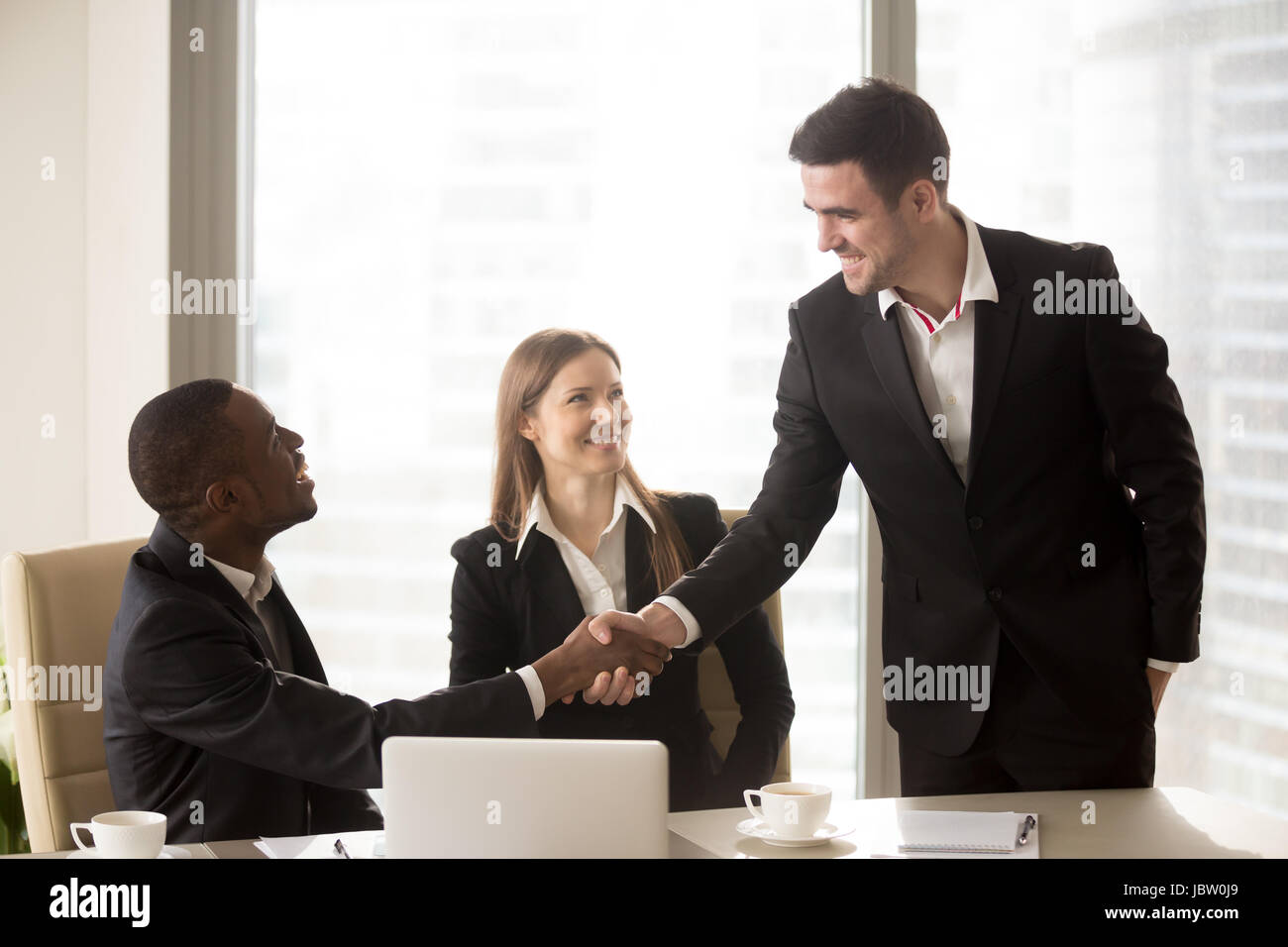 South American and Caucasian businessmen handshaking en séance officielle, l'accueil des nouveaux entrepreneurs Photo Stock