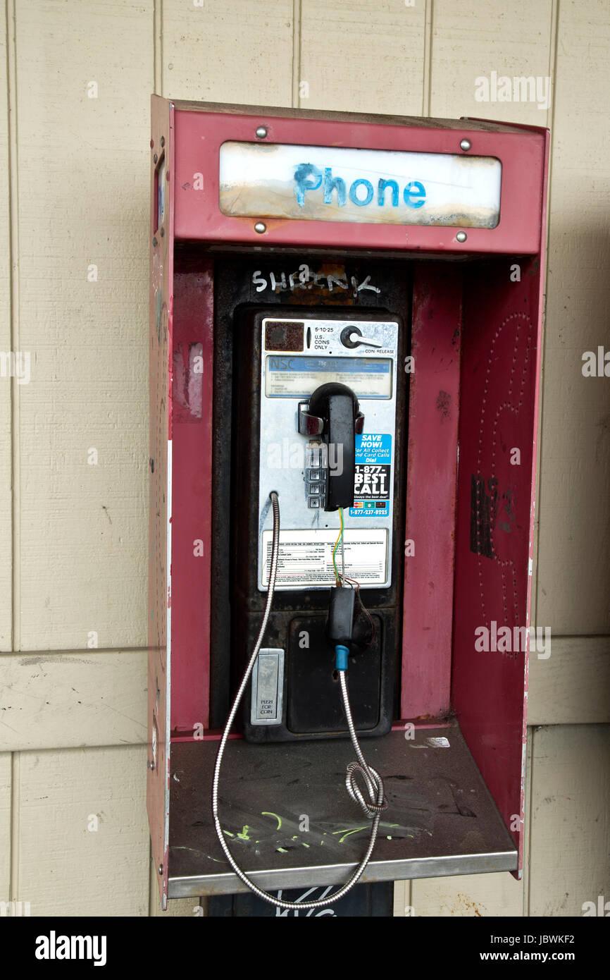 Coin operated abandonnés téléphone public payant avec coin presse, des graffitis. Photo Stock