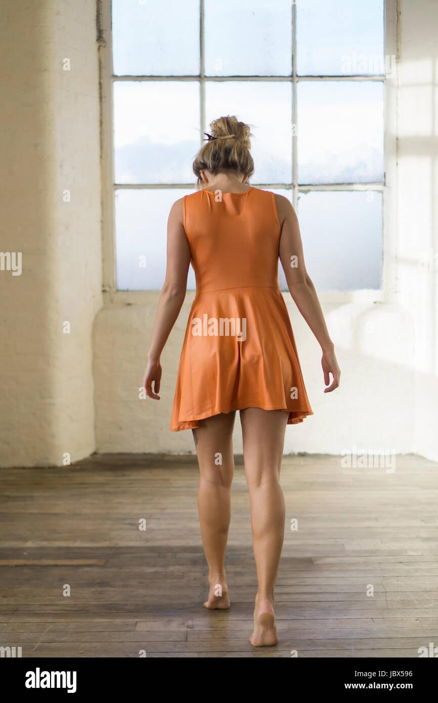 Vue arrière d'un jeune blond caucasian woman wearing une courte robe d'été orange à Photo Stock