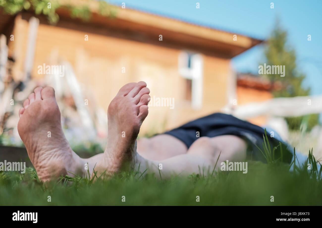 L'homme portant sur la pelouse. Il vous détendre sur la nature en été. Rechercher sur sky Photo Stock