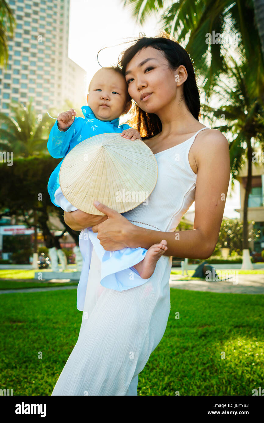 Une mère tient sa petite fille dans un Vietnam clothers aodai dans ses bras sur la plage près de palms Banque D'Images
