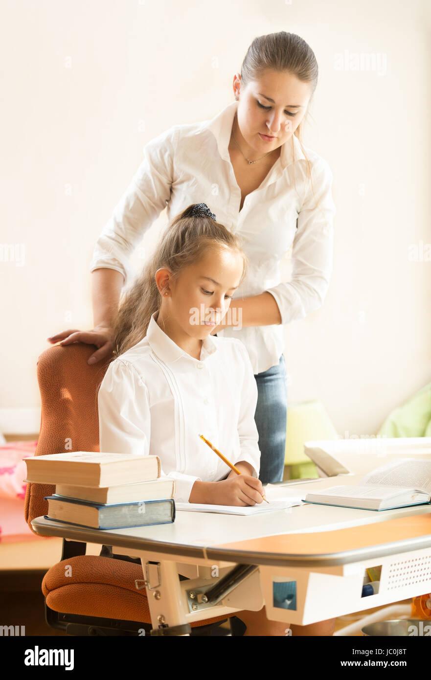 Écolière Cute faire leurs devoirs tout en regardant sa mère Banque D'Images