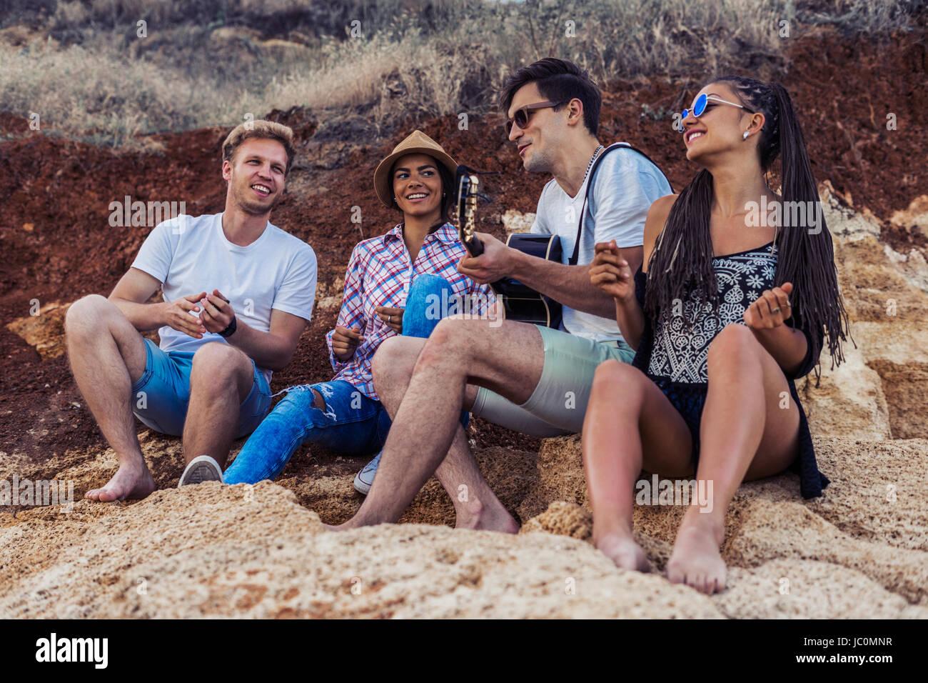 Amis assis sur des pierres sur la plage. l'homme est de jouer de la guitare. Photo Stock