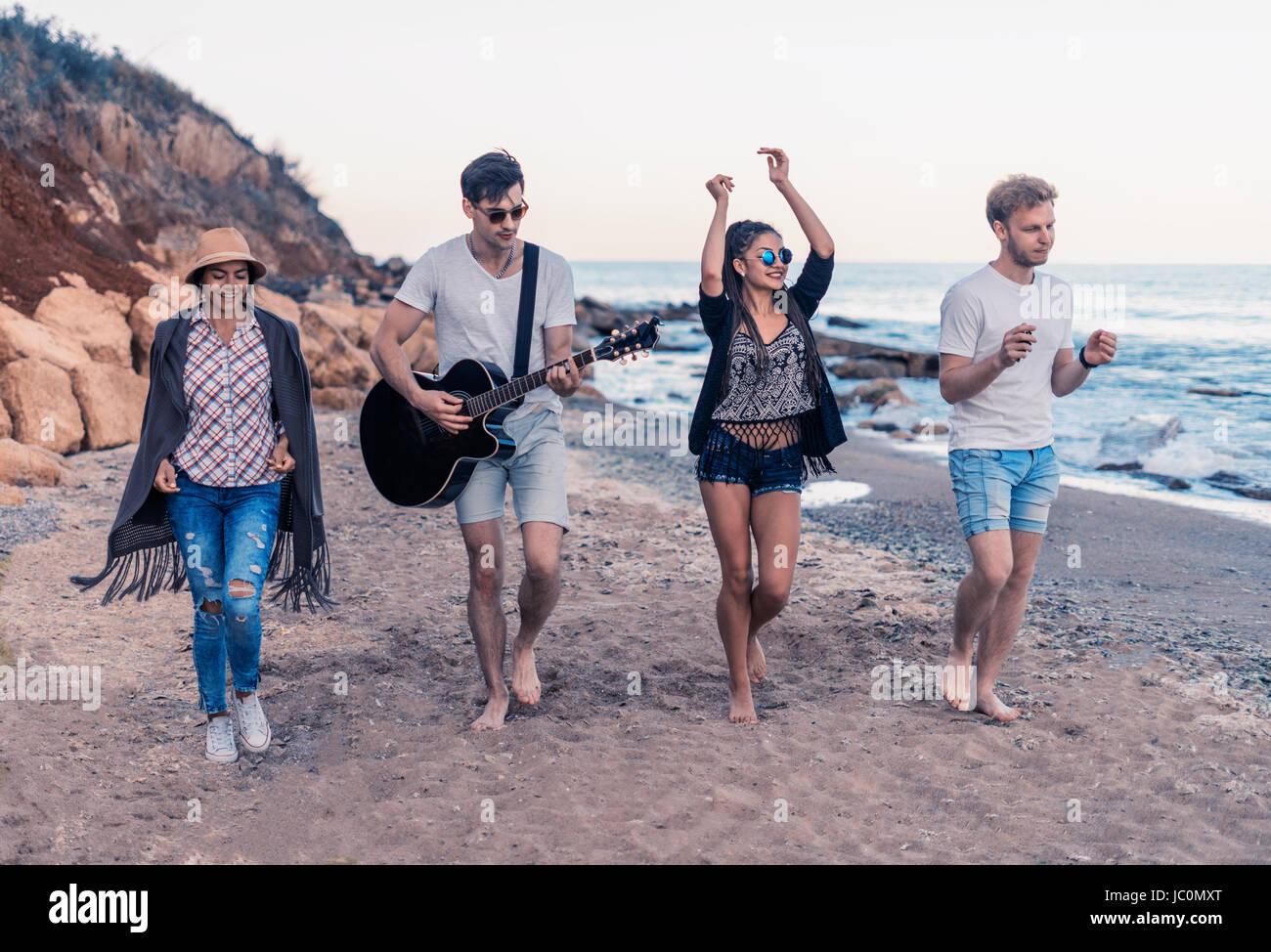 Groupe de jeunes et joyeux amis walking on beach Photo Stock