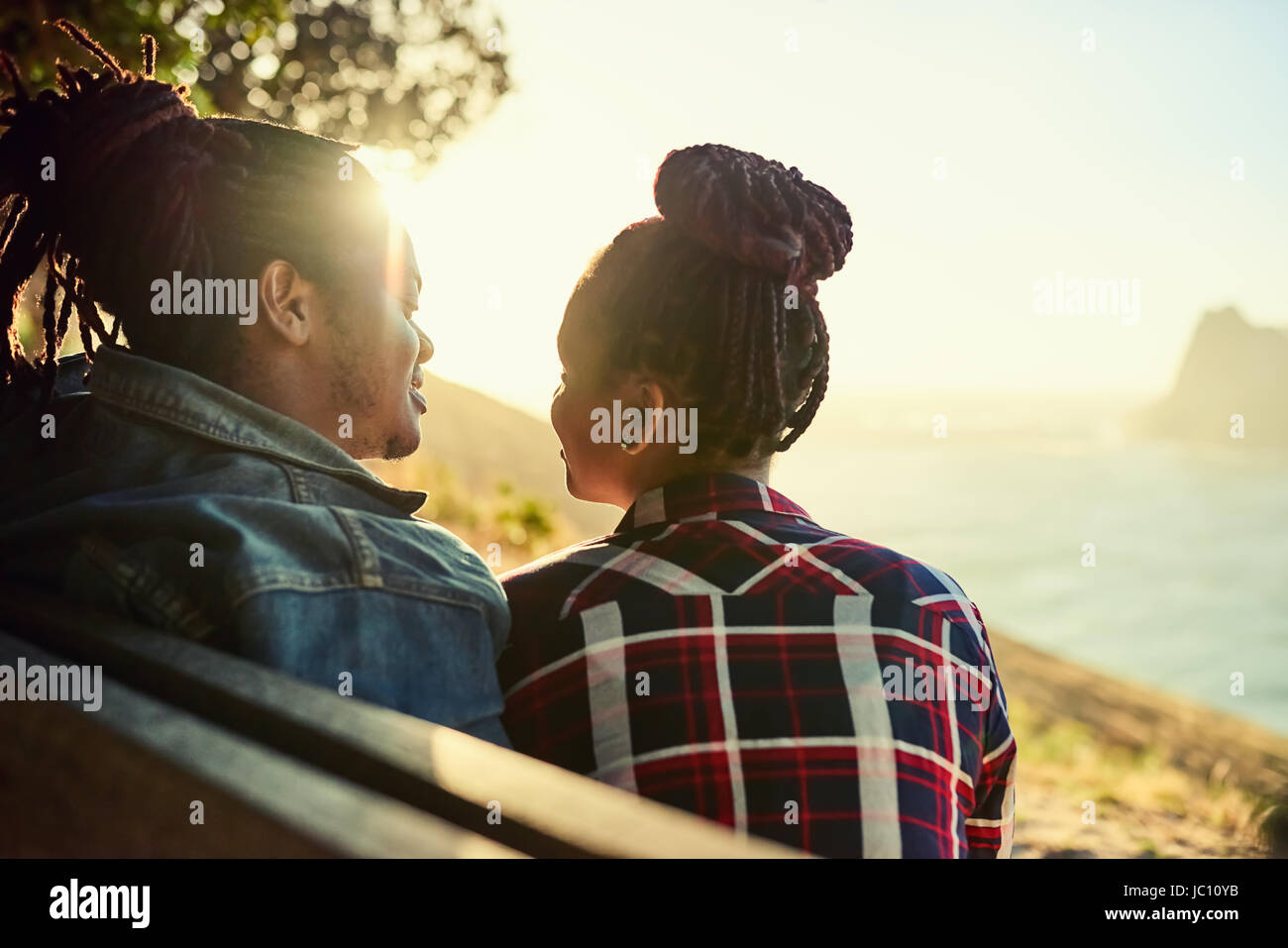 Couple d'origine africaine assise sur un banc public viewpoint Photo Stock