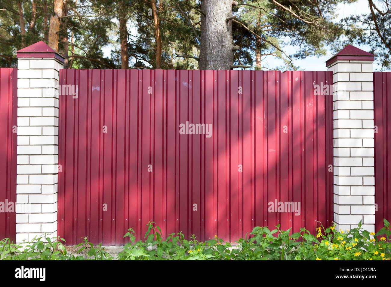 Clôture faite de panneaux métalliques de couleur rouge à l'extérieur Banque D'Images