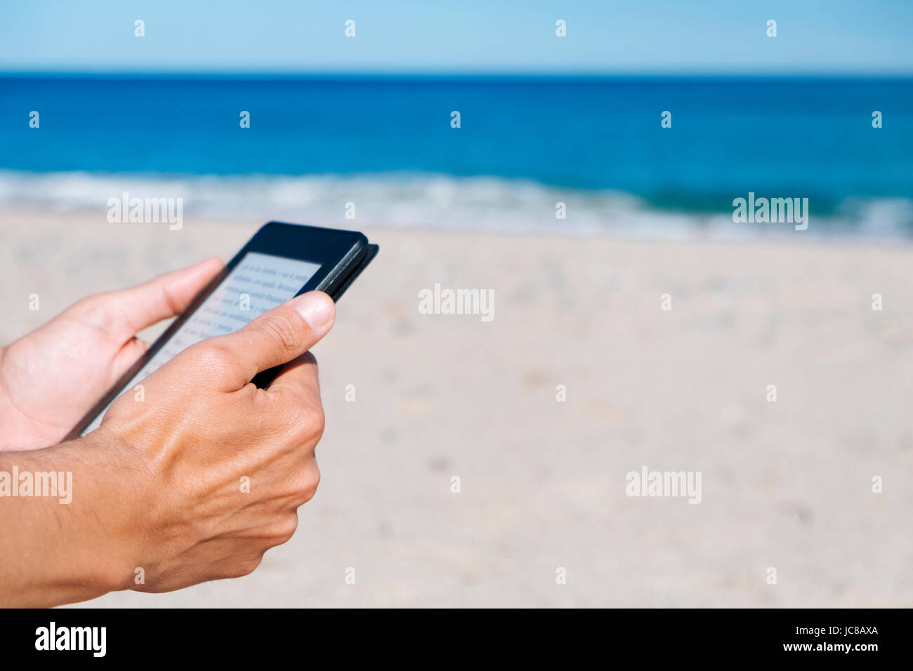 Libre d'un jeune homme de race blanche dans une tablette de lecture ou e-reader sur une plage de sable blanc Photo Stock