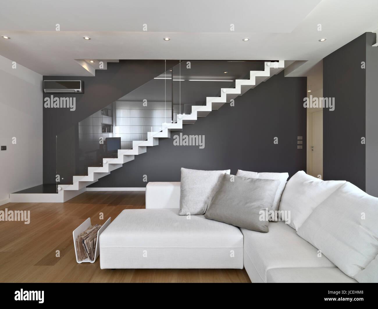 Canapé en tissu dans le salon moderne avec escalier et ...