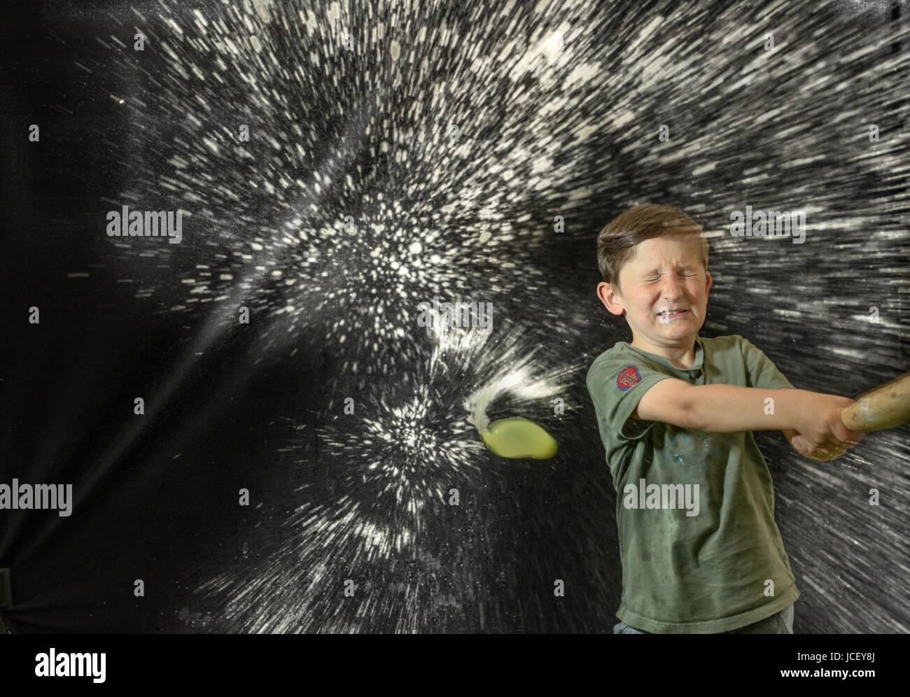 Jeune garçon, les yeux fermés, et avec un regard de détermination sur son visage, touchera un ballon Photo Stock