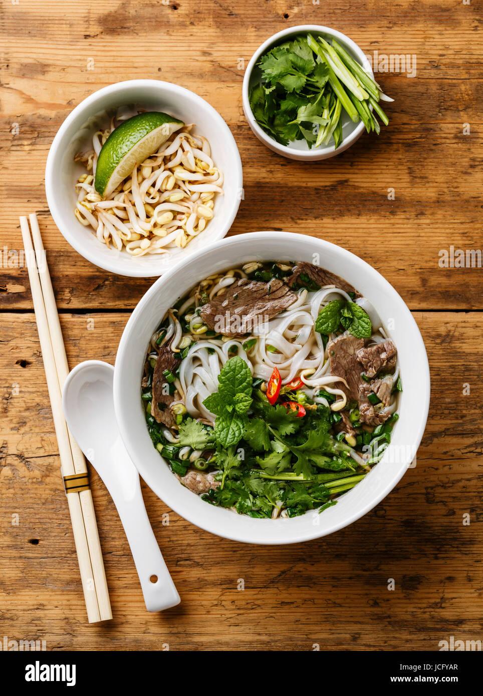 Pho Bo soupe vietnamienne au bœuf et les semis de soja sur fond de bois Photo Stock