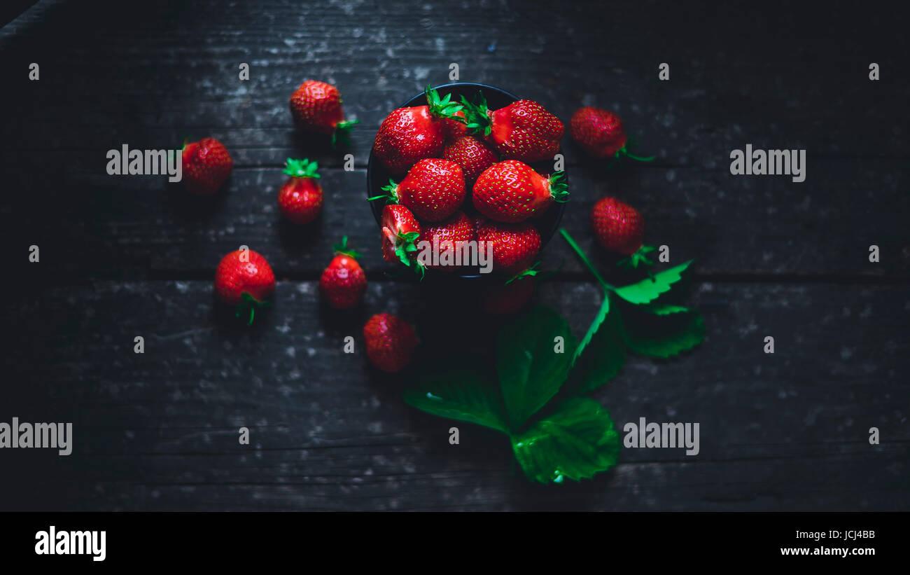 Dans un bol de fraises avec des feuilles sur une vieille planche de bois Photo Stock