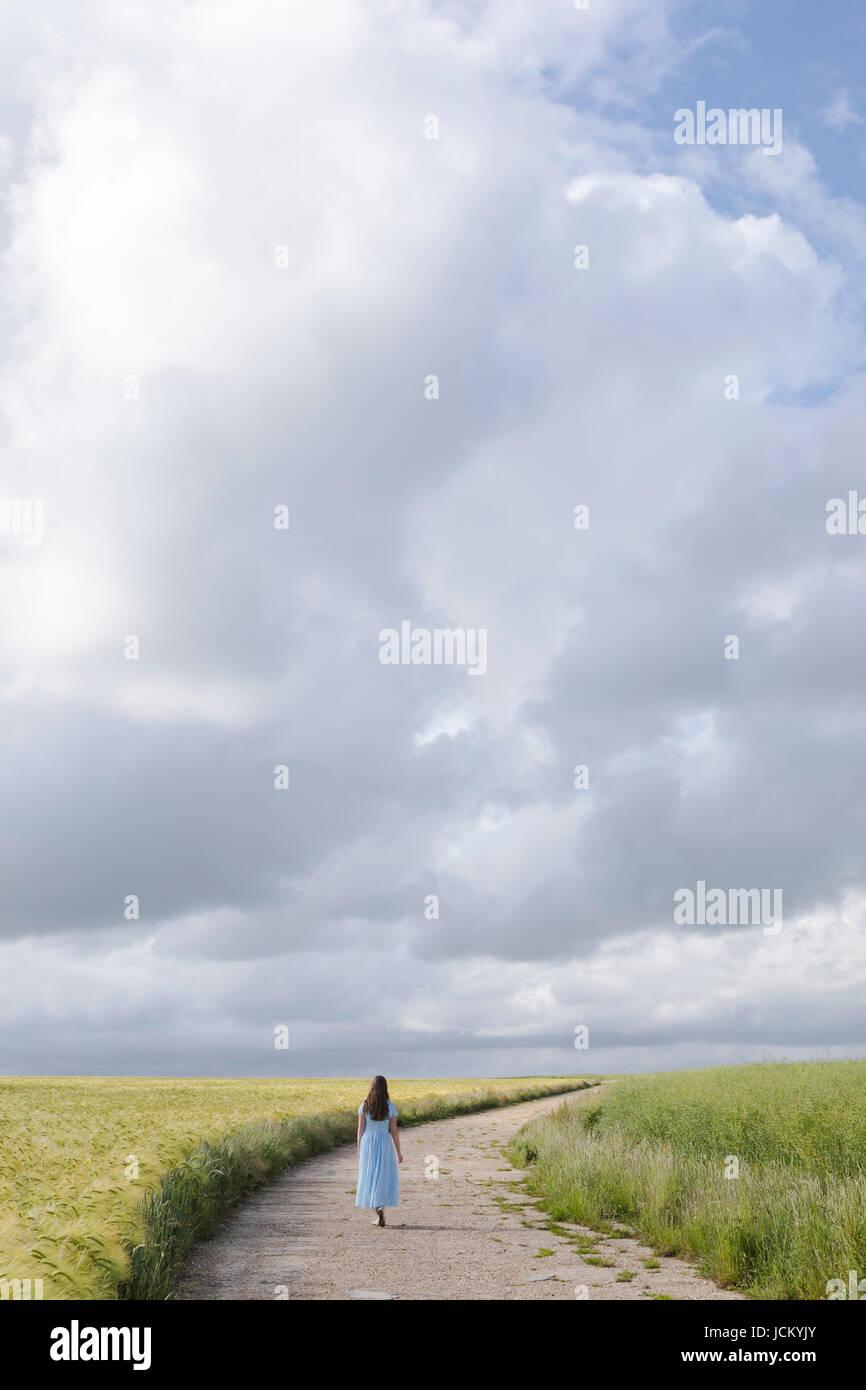 Une femme dans une robe bleue marche sur un chemin à travers les champs Banque D'Images