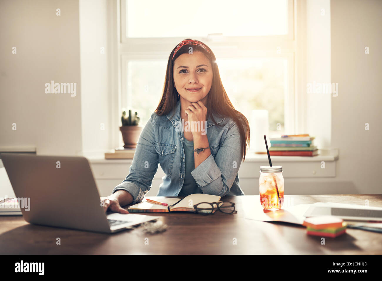Pretty young businesswoman looking at camera sitting at laptop in office. Photo Stock
