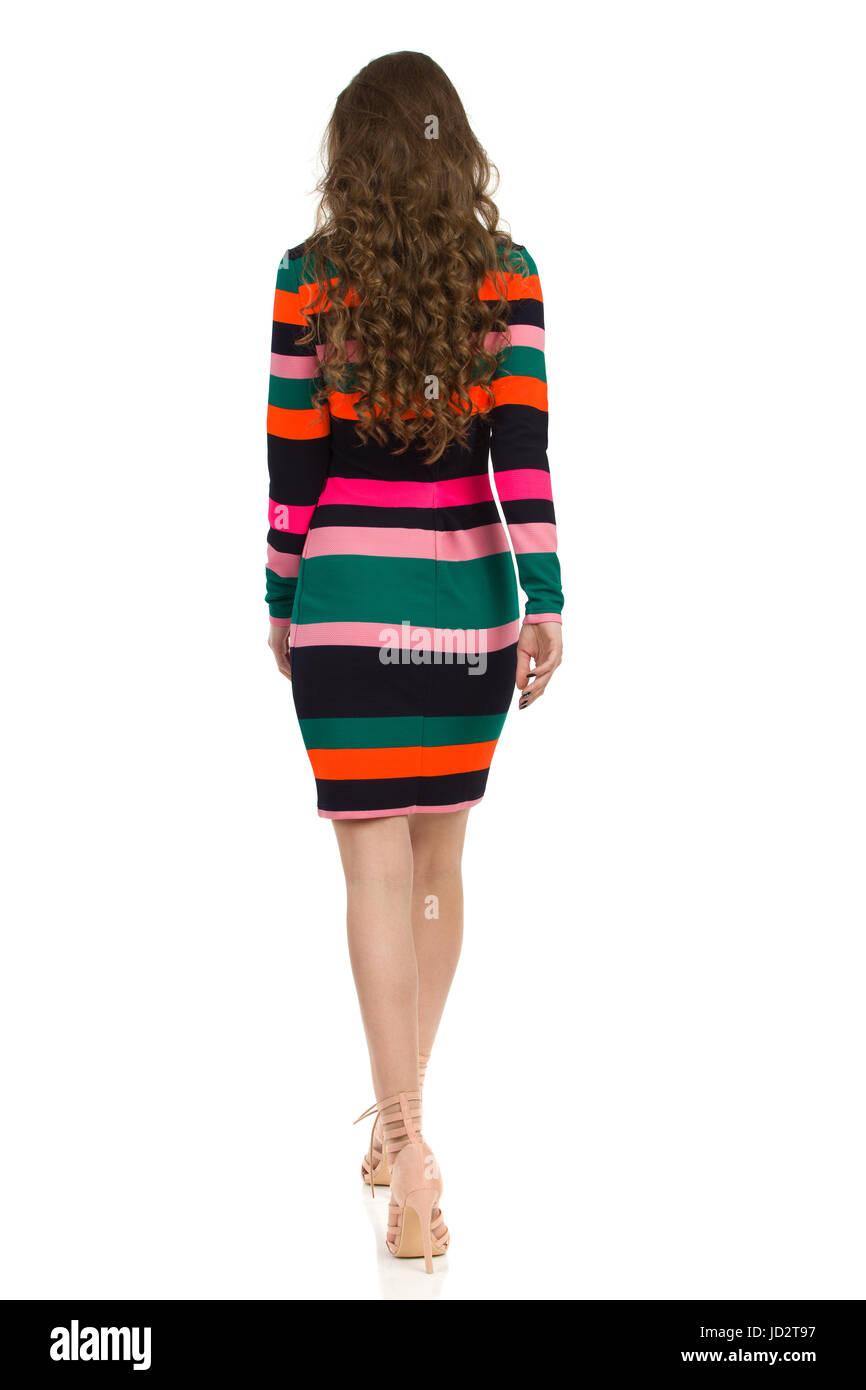 6cd1f546411 Vue arrière de la marche jeune femme en robe à rayures colorées et de hauts  talons