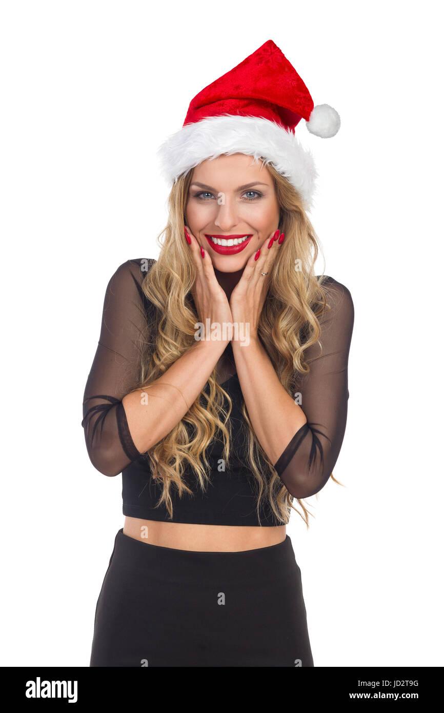 Jeune femme blonde extatique à Santa's hat et robe noire tenant la tête dans les mains et sourit. Photo Stock