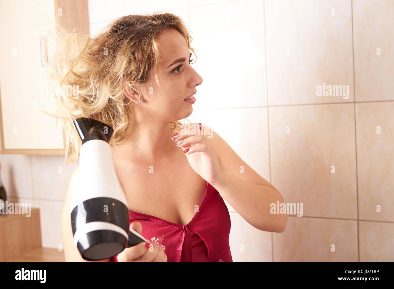 Une jeune femme vêtue d'une nuisette rouge sèche séchage dans la salle de bain le matin Photo Stock