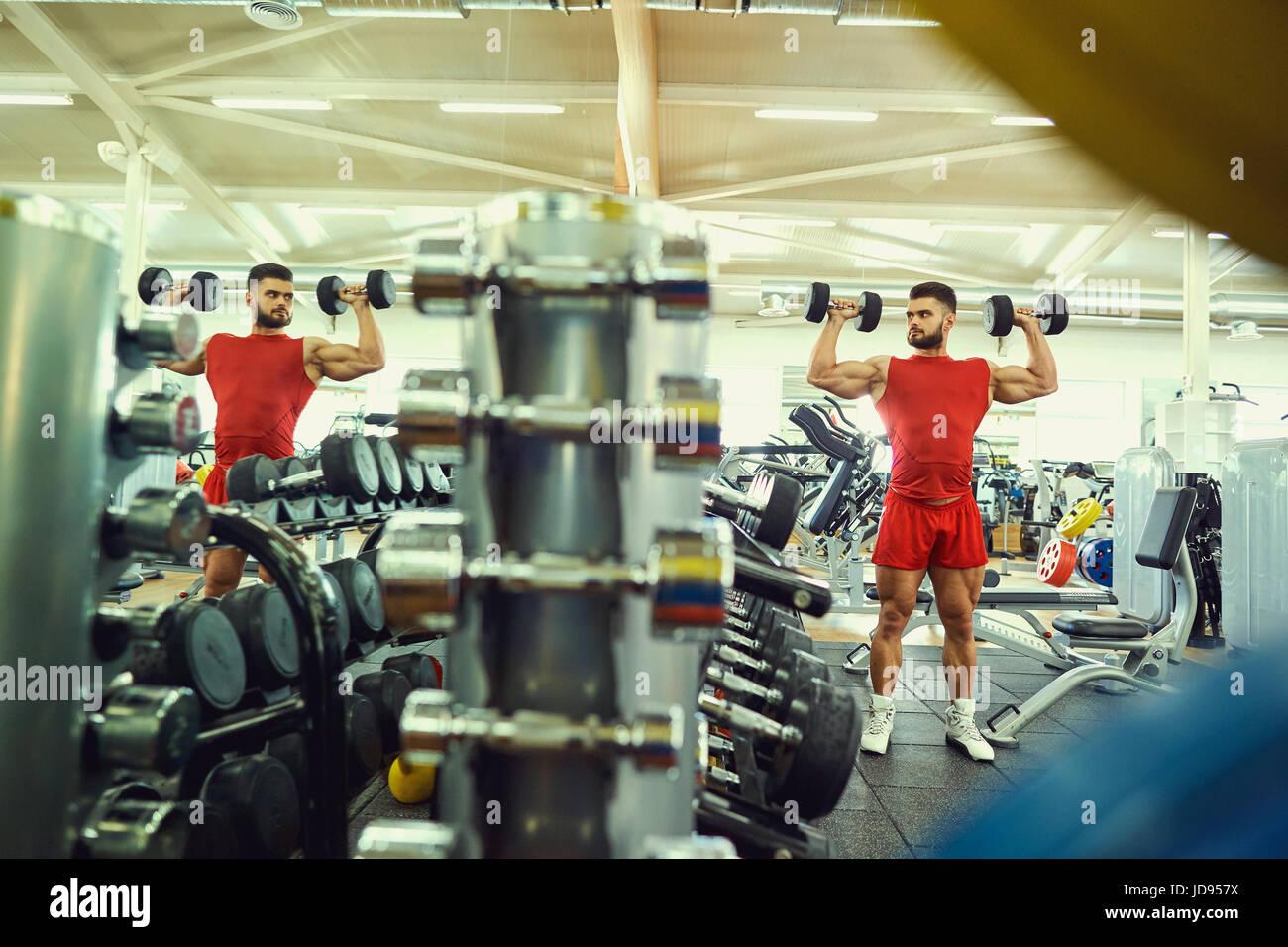 Faire des exercices avec haltères bodybuilder dans la salle de sport Photo Stock