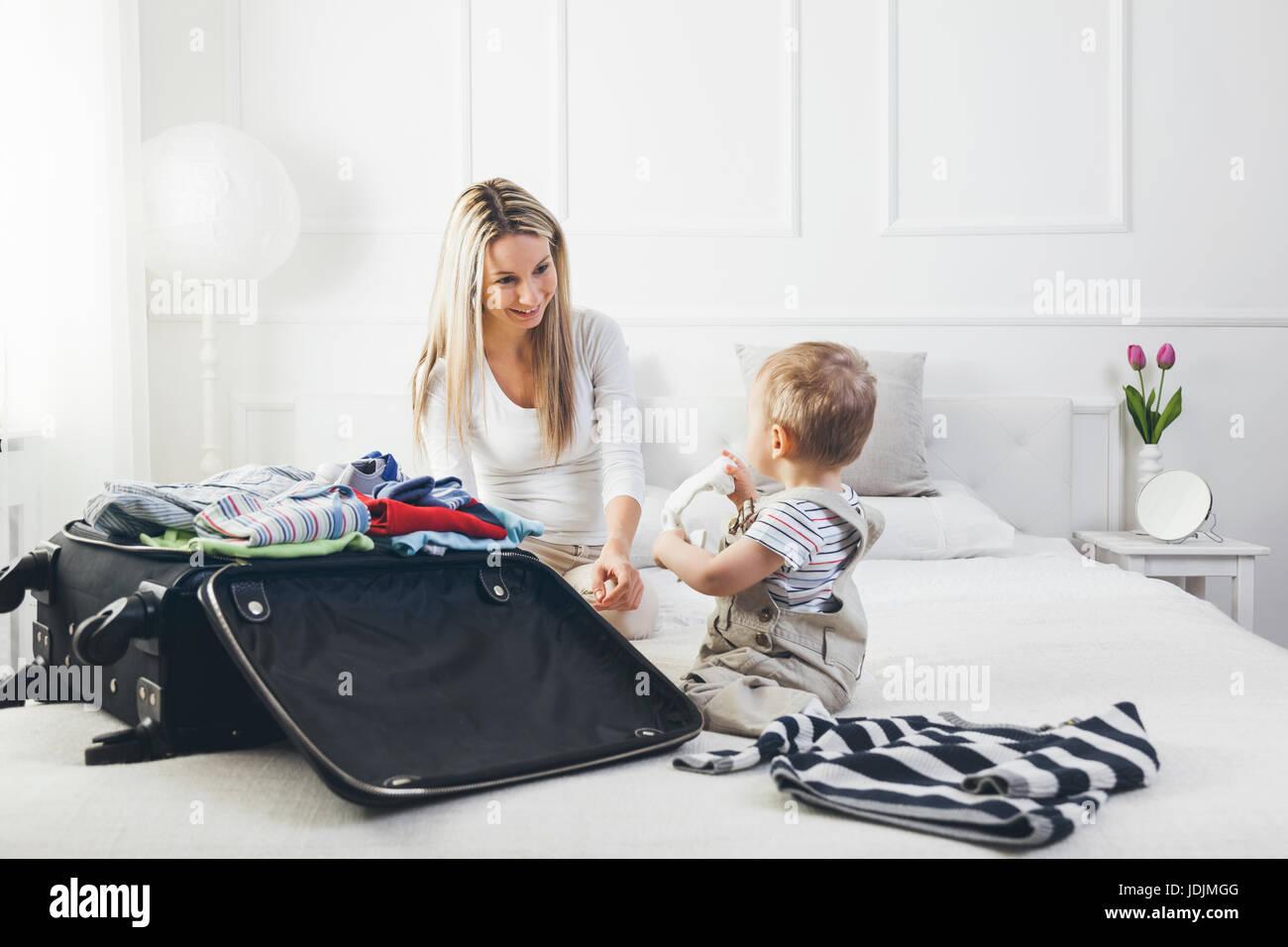 Voyagez avec des enfants. Mère heureuse avec son enfant vêtements d'emballage pour les vacances Photo Stock