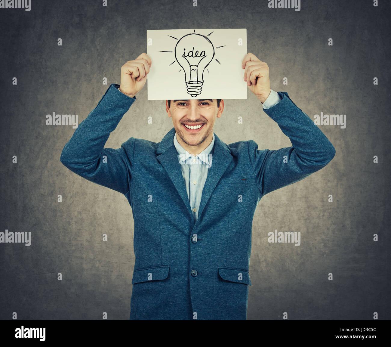 Smiling businessman holding enseignant ou un livre blanc au-dessus de sa tête avec une ampoule de croquis. Photo Stock