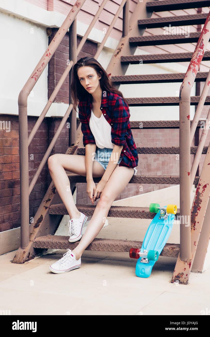 Belle jeune fille en chemise à carreaux et jeans taille basse short shorts  et baskets blanches s asseoir sur l escalier avec son mini bleu skateboard  ... d56685338a1