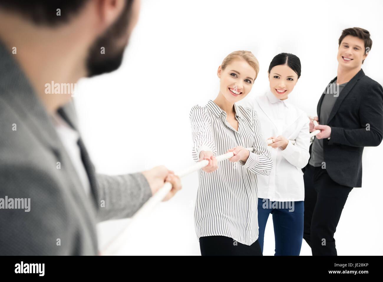 Groupe de gens d'affaires tirant plus de corde isolated on white Photo Stock