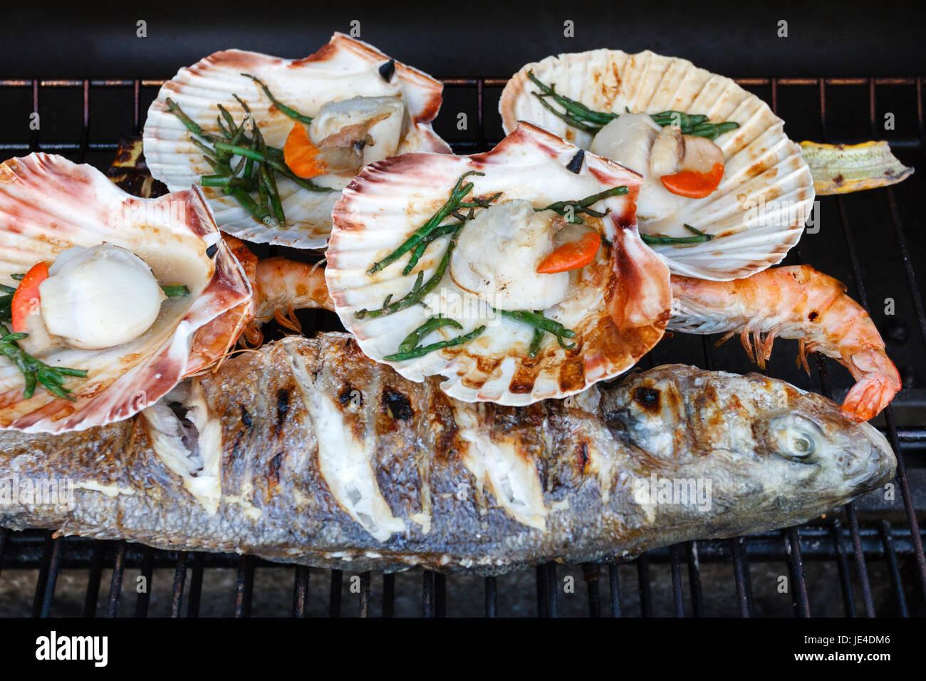 Poissons et fruits de mer cuits sur un barbecue en Angleterre, Royaume-Uni Photo Stock