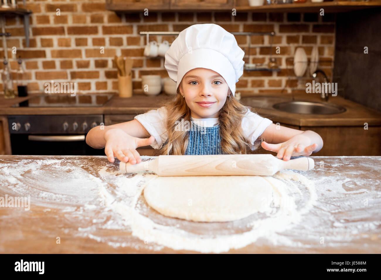 Girl en chef hat le déploiement de pâte à pizza crue Photo Stock