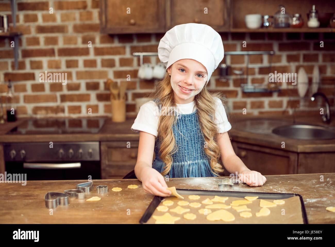 Portrait de petite fille en faisant des cookies en forme de chapeau de chef de cuisine Photo Stock