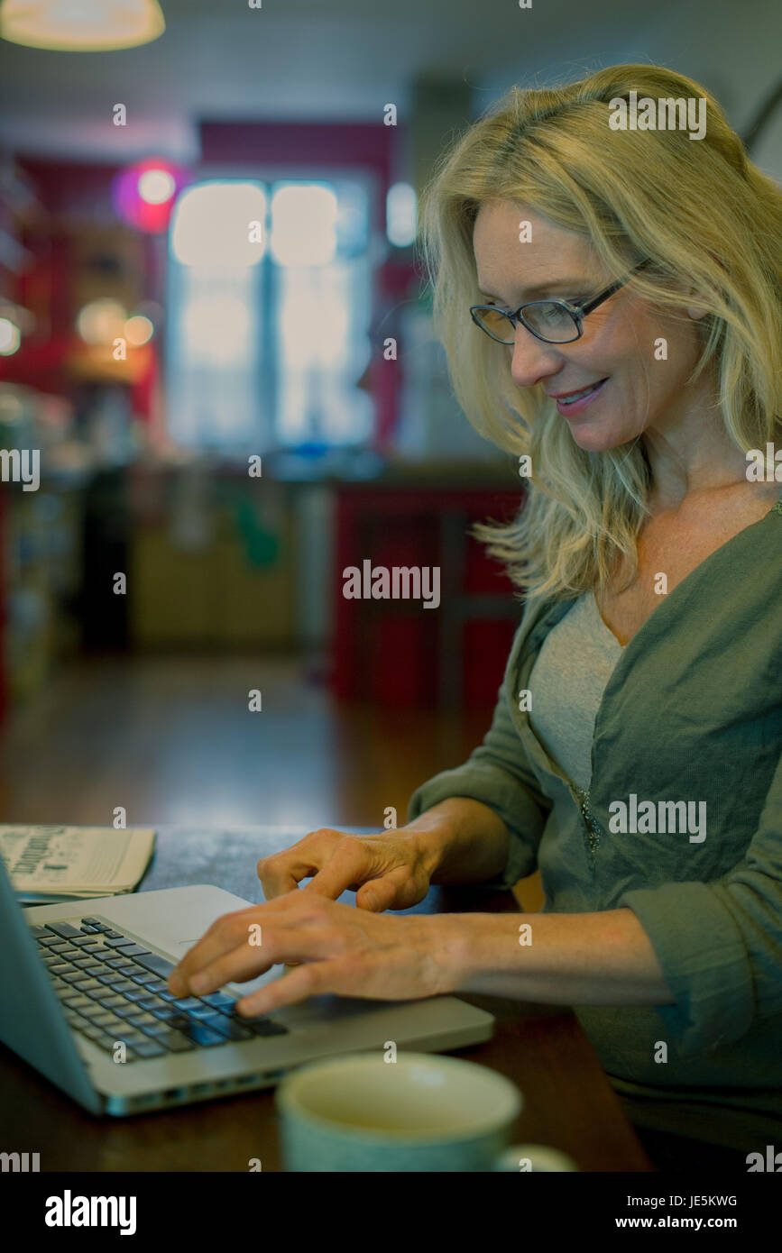 Mature Woman using laptop computer at home Banque D'Images