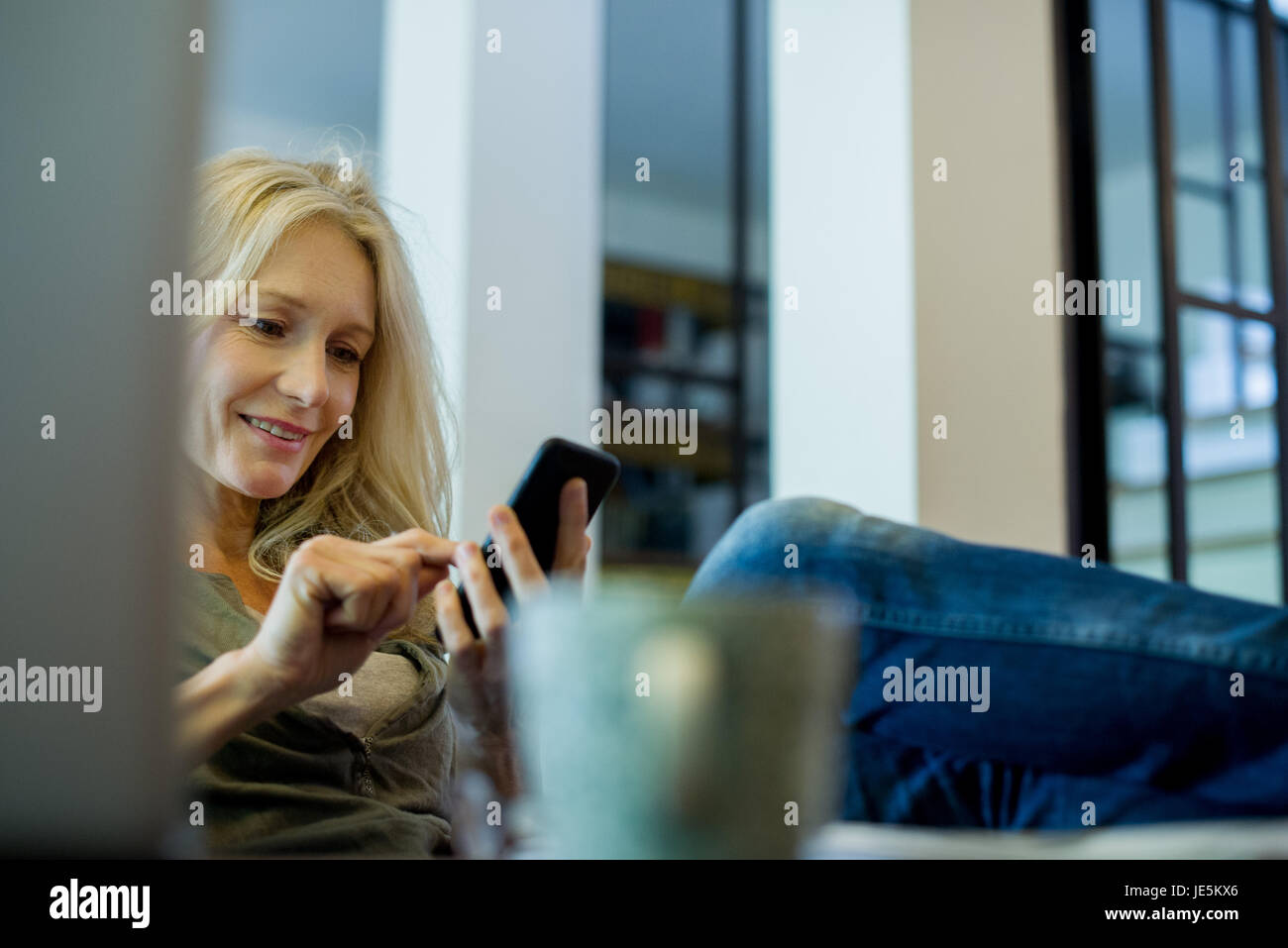 Mature Woman relaxing with smartphone Photo Stock