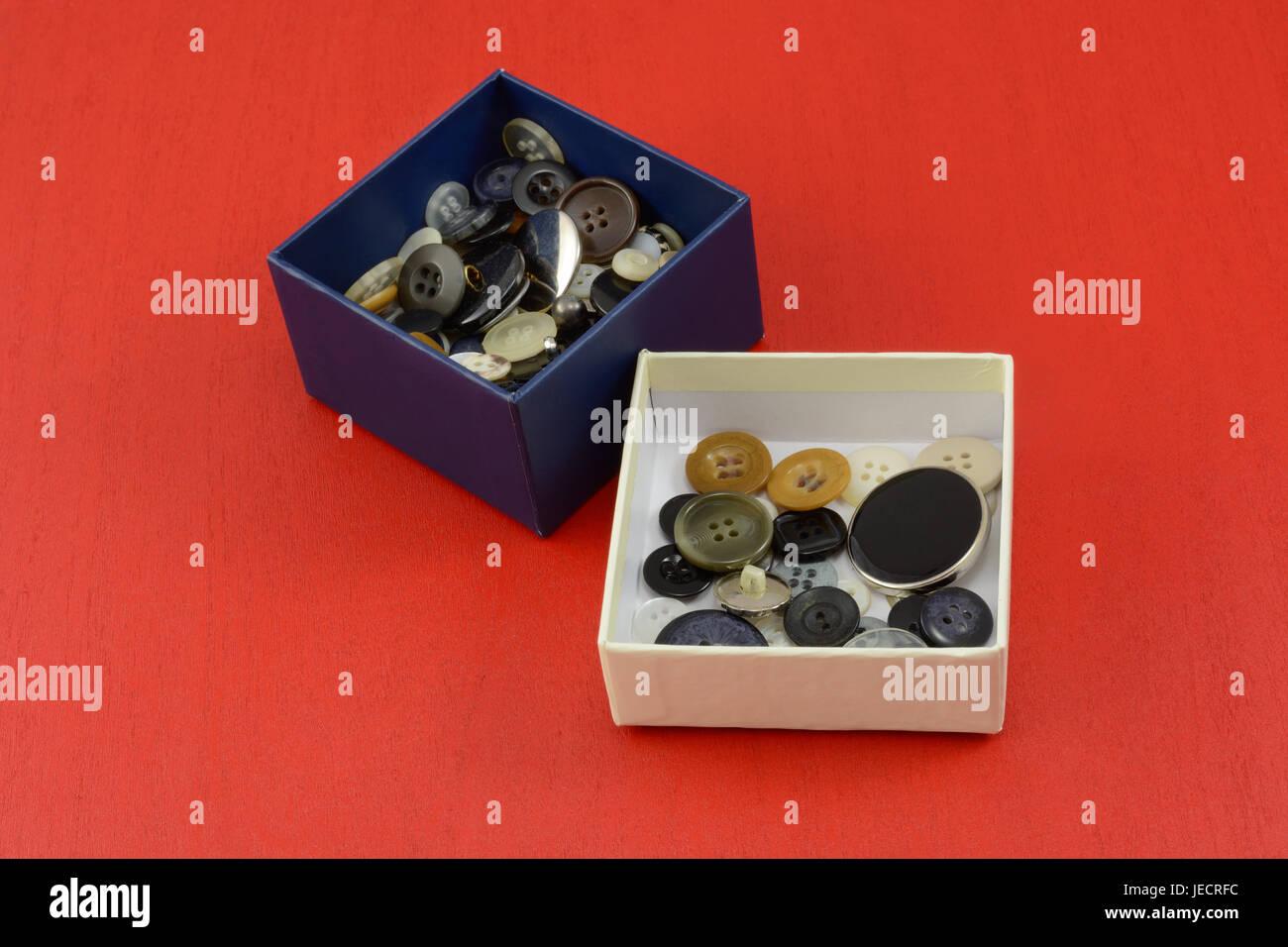Collection de boutons dans les boîtes bleues et blanches sur fond de bois rouge Banque D'Images