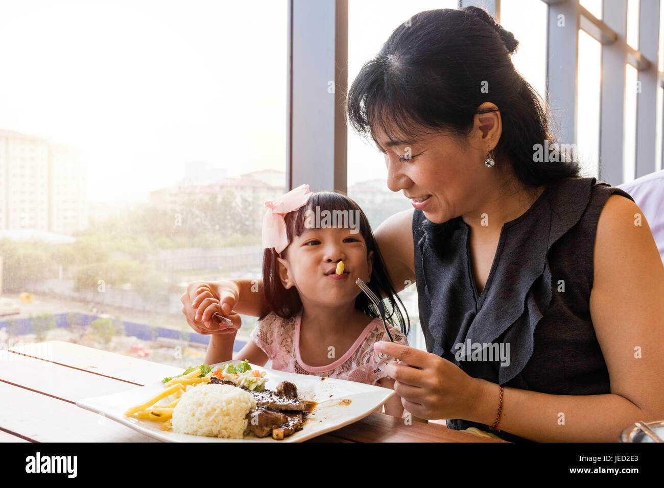 Chinois asiatique mother and daughter eating steak dans le restaurant. Photo Stock